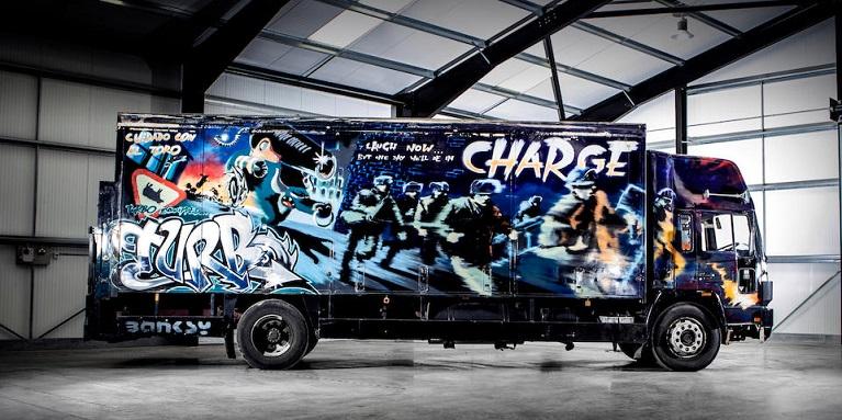 Auto e street art un camion Volvo con in primo piano il murale di Banksy intitolato Laugh Now But One Day We'll Be In Charge