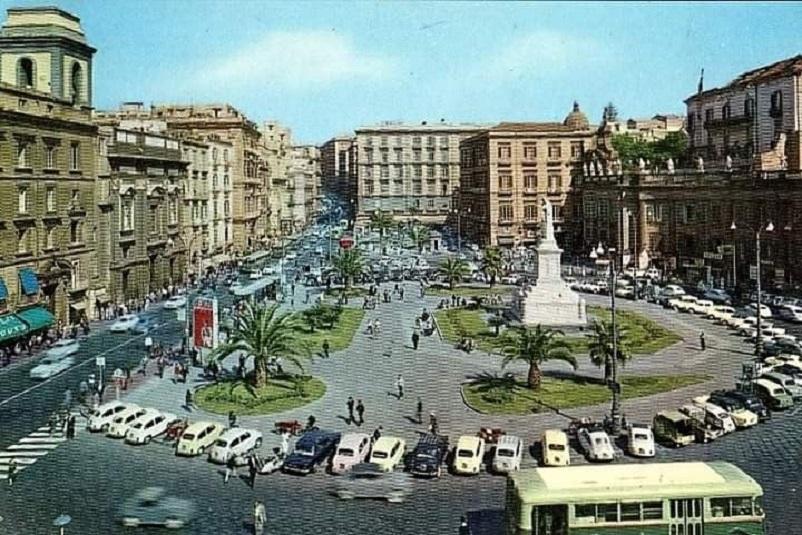 """Foto in bianco e nero Piazza Dante a Napoli, in un set allestito con auto e mezzi degli anni '70 per la serie """"l'amica geniale""""."""