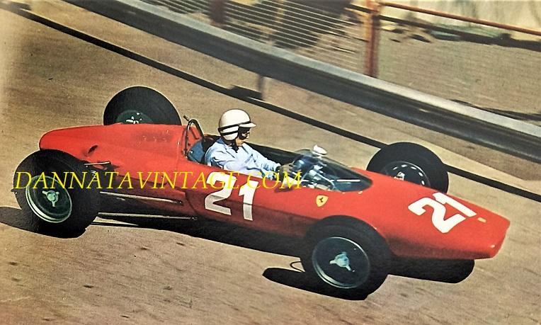 Si correva, John Surtees alla guida di una Ferrari prima di affrontare la Curva del Tabaccaio al GP di Monaco del 1963, era la sua prima gara su una auto dopo aver abbandonato le moto da campione del mondo. Motore posteriore da sei cilindri a V 1476 Cc e 210 cavalli a 10.200 la potenza.